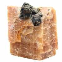 Svarta glimmerkristaller på på orange kalcitblock